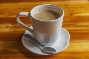 creme de café preto em copo branco na mesa de madeira laos. foto