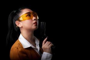 Asea mulher vestindo um terno amarelo com uma das mãos segurando uma pistola em fundo preto foto