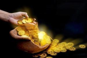 moedas de ouro em mãos sobre lotes empilhando moedas de ouro em um frasco de tesouro quebrado com fundo branco foto
