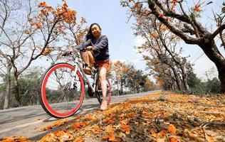 jovem feliz, aproveitando a atividade de lazer ao ar livre, andando de bicicleta e sorrindo de felicidade, os estilos de vida saudáveis cheios de um lindo fundo de flor de laranjeira foto