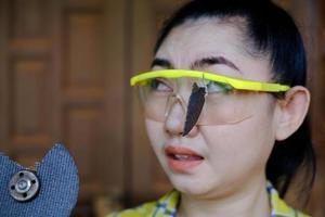usar óculos de segurança salvou esta mulher técnica está olhando enquanto trabalha porque o disco de corte do plugin está quebrado foto