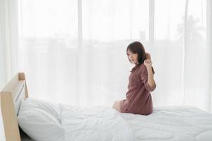 mulher asiática na cama e acordando de manhã foto