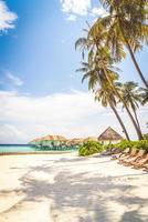 cadeiras de praia com ilha tropical das Maldivas praia e mar - conceito de plano de fundo de férias de férias foto