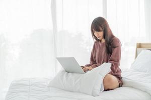 mulher asiática trabalhando com laptop na cama em casa foto