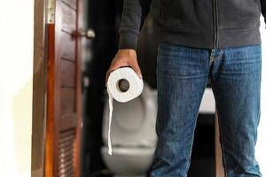 homem segurando rolo de papel higiênico no banheiro foto