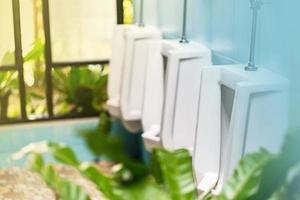 fila de mictórios brancos no banheiro masculino foto