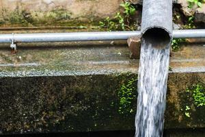 fluxo de águas residuais para o esgoto, tubos de esgoto para um pequeno canal foto