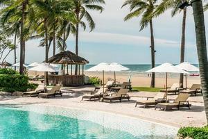 espreguiçadeiras ou camas e guarda-sóis ao redor da piscina com fundo do mar - feriados e conceito de férias foto