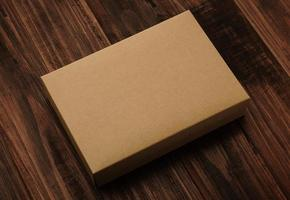 maquete de caixa de papelão com fundo de madeira foto