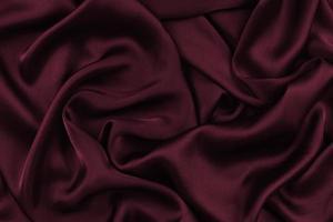 pano de cetim sedoso abstrato, cortina de tecido de tecido com dobras onduladas vincadas. com ondas suaves, ondulando ao vento. textura de papel amassado foto