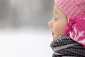 retrato de uma menina em close-up rosa. uma criança gosta da queda de neve. feriado de Natal foto