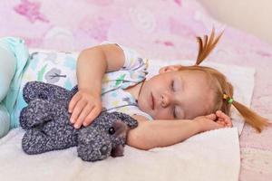uma criança pequena está dormindo em uma cama com brinquedos aninhados. infância. foto