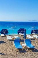 espreguiçadeiras azuis nas águas turquesa da praia de elli em rhodes, grécia foto