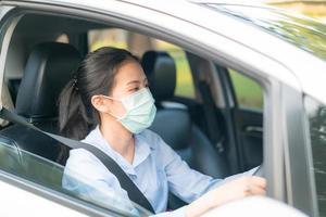 Linda mulher asiática dirigindo um carro usando máscara, indo para fora, mantenha-se saudável, protegendo contra o vírus covid-19 do coronavírus foto