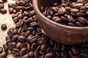 grãos de café em uma tigela de madeira no fundo branco foto