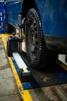 close-up de um pneu preso por uma niveladora que passa o alinhamento automático das rodas na garagem, garagem e ferramentas para o mecânico. foto