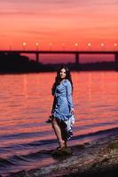 linda jovem com longos cabelos escuros ondulados em pé na margem do rio foto