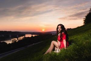 linda jovem sentada em uma encosta coberta com grama verde foto