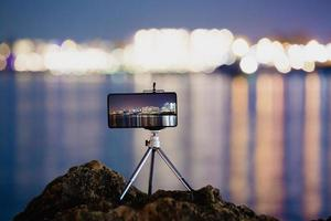usando um smartphone em um tripé com longa exposição do mar à noite foto