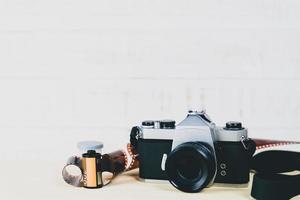 velha câmera de filme 35mm slr e um rolo de filme com fundo de madeira. conceito de fotografia flim. foto