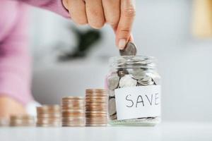 mulheres entregam colocando moedas de dinheiro em um frasco de vidro para economizar dinheiro. economizando dinheiro e conceito financeiro foto