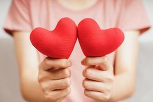 mulher segurando um coração vermelho, amor, seguro de saúde, doação, voluntário de caridade feliz, dia mundial da saúde mental, dia mundial do coração, dia dos namorados foto