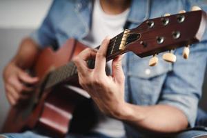 Desfrute de um belo homem asiático praticando ou tocando violão no sofá da sala de estar foto