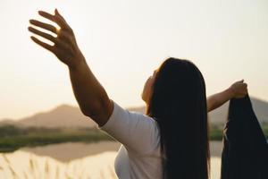 mulher de negócios feliz abrindo os braços e observando a silhueta da montanha. conceito de sucesso empresarial, emoções de liberdade foto