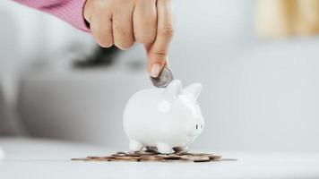 close up da mão de mulher de negócios, colocando moedas de dinheiro no cofrinho para economizar dinheiro. economizando dinheiro e conceito financeiro foto
