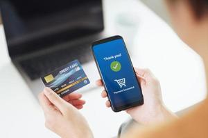 jovem segurando um cartão de crédito e usando o telefone inteligente para fazer compras online, banco na internet, comércio eletrônico, gastar dinheiro, trabalhar em casa. foto