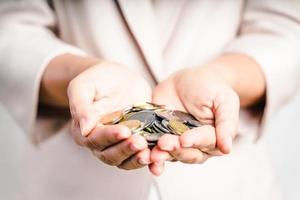 close up das mãos de mulher de negócios segurando moedas no fundo branco. economizando dinheiro, conceito finacial. foto