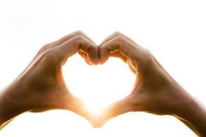 mão em forma de coração com o nascer do sol no fundo do céu. conceito de amor. foto