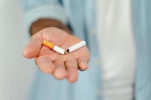 close up da mão do homem segurando o cigarro quebrado na mão. conceito de parar de fumar, mundo sem dia do tabaco. foto