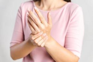 closeup jovem mulher segura o pulso em fundo branco. lesão na mão, sensação de dor. cuidados de saúde e conceito médico. foto