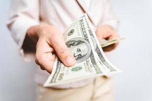 close up das mãos de mulher de negócios propondo dinheiro nos notas de dólar em fundo branco. conceito de dinheiro. foto