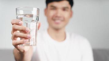 bonito homem asiático bebendo um copo d'água no sofá da sala foto