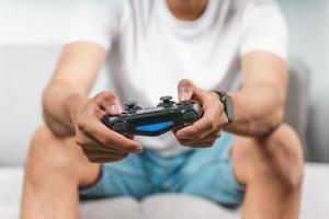 animado jovem bonito segurando o controle do joystick, jogando videogame, sentado no sofá em casa foto