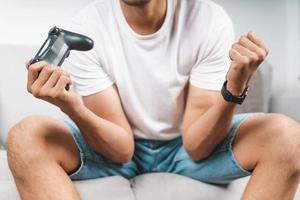 animado jovem bonito jogando videogame e levantando os punhos, sentado no sofá em casa. foto
