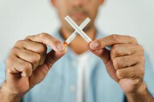 mão do homem segurando cigarros cruzados. conceito de parar de fumar, mundo sem dia do tabaco. foto