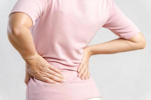 jovem sentindo dor nas costas em fundo branco. conceito de saúde e médico. foto