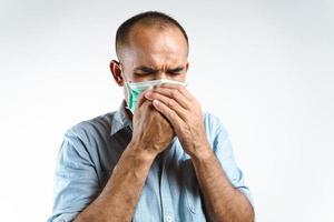 homem usando máscara facial, espirrando ou tossindo na mão para evitar a propagação do vírus covid-19 ou vírus corona em fundo branco. foto