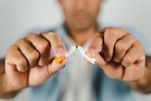 mão de homem esmagando cigarro, conceito de parar de fumar, mundo sem dia de tabaco. foto