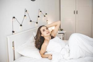 bela jovem acordando em uma cama confortável com lençóis brancos e frescos. foto