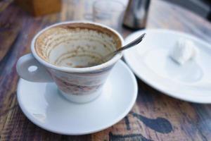 copo branco com sobras de café na mesa foto