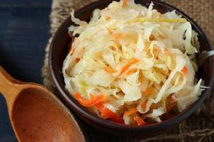 Salada de chucrute em um prato e uma colher de pau foto