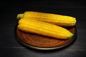 espigas de milho cozido amarelo em um fundo escuro. foto