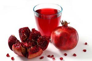 suco de romã e frutas sobre branco foto