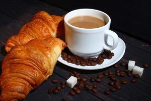 cappuccino em uma xícara e croissant. pequeno-almoço popular. foto