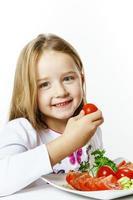 menina bonitinha com prato de legumes frescos foto
