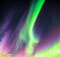 aurora boreal ou aurora boreal verde e roxa com estrelas no céu noturno foto